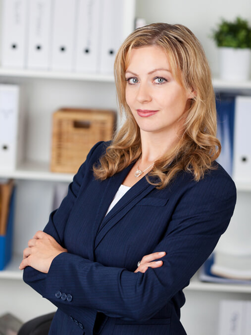 Event Moderation von Carmen Hentschel, hier im blauen Hosenanzug im Büro