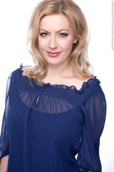 Event Moderation von Carmen Hentschel, Foto lächelnd mit blauer Bluse und offenem Haar