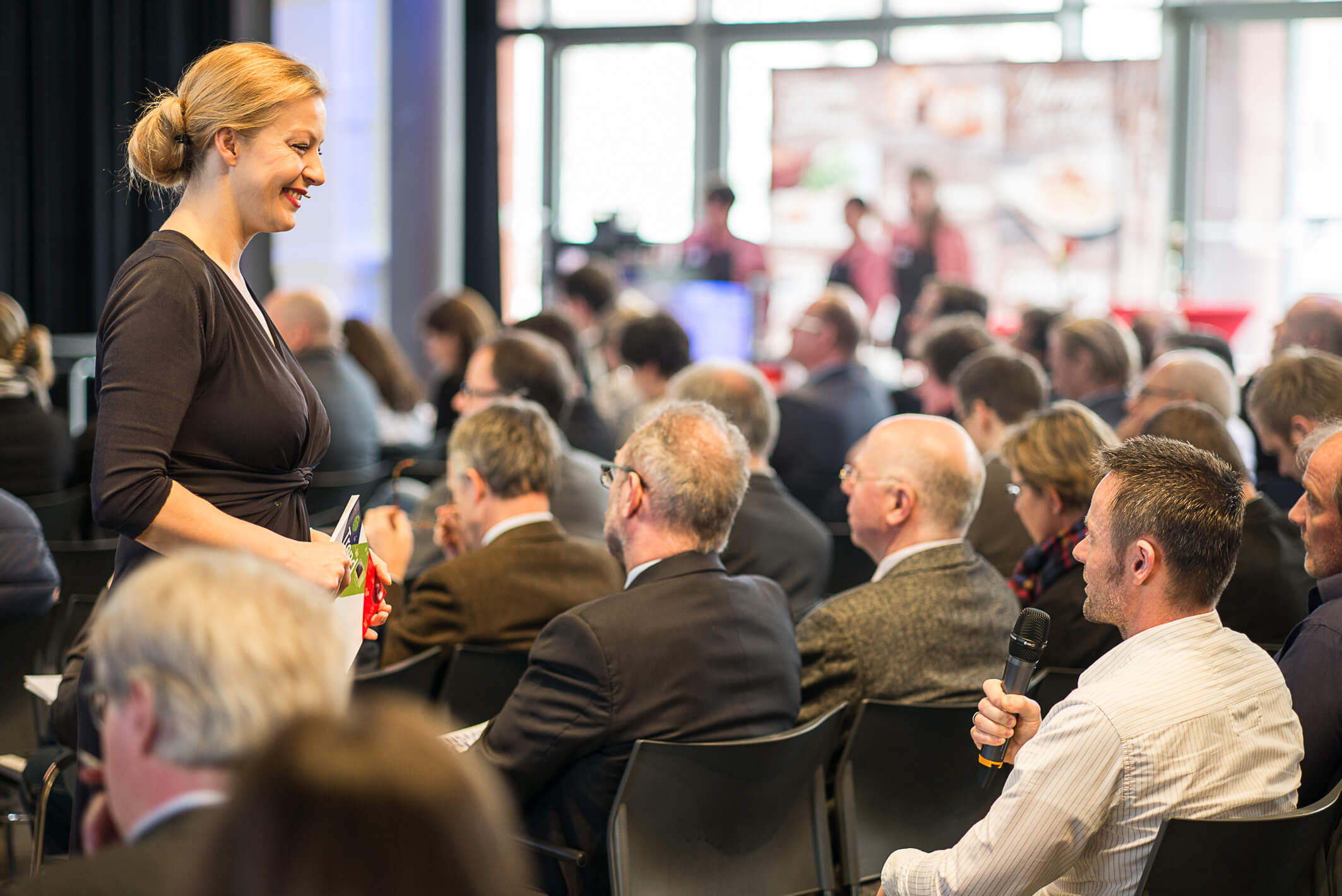 Moderatorin Podiumsdiskussion Carmen Hentschel interviewt Menschen im Publikum bei einer Veranstaltung