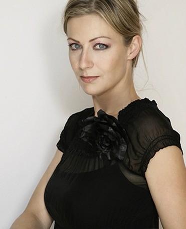 Event Moderation von Carmen Hentschel Portraitfoto mit schwarzer Bluse und hoch gesteckten Haaren